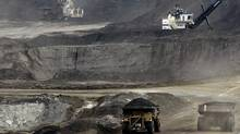 Mining trucks carry loads of oil-laden sand at the Albian Sands oils sands project in Fort McMurray, Alta. (JEFF McINTOSH/AP)