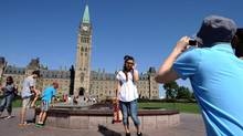 Japanese tourists pause to take pictures as they visit Parliament Hill in Ottawa, on August 17, 2011. Summer students hired as tourist guides for Parliament Hill and area have been trained to praise the Senate and disdain democracies with three or more political parties. (Sean Kilpatrick/The Canadian Press)