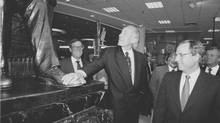 In a photo from June 5, 1997, the new president of Eatons, George Kosich, looks up at the statue of the founder of the store, Timothy Eaton. In background on the left is Fred Eaton. On the front right, George Eaton. Behind George on left is Thor Eaton and far right is John Craig Eaton. (Tibor Kolley/The Globe and Mail)