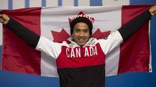 Canadian speed skater Gilmore Junio holds up a Canadian flag following a news conference at the Sochi Winter Olympics Sunday Feb. 16, 2014 in Sochi, Russia. (Adrian Wyld/Canadian Press)
