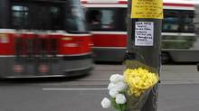 Flowers can be seen tied to a pole on Dundas St., at Grace St., where 18 year old Sammy Yatim was shoot by Toronto Police, Toronto July 29, 2013. (Fernando Morales/The Globe and Mail)