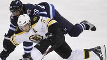 Winnipeg Jets' Johnny Oduya (29) battles with Boston Bruins' Patrice Bergeron during second period NHL action in Winnipeg Tuesday, December 6, 2011. THE CANADIAN PRESS/Trevor Hagan (Trevor Hagan/CP)