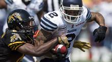 Hamilton Tiger-Cats defensive back Armando Murillo tries to strip the ball as he tackles Toronto Argonauts wide receiver Chad Owens (2) during first half CFL action in Hamilton, Ontario on Monday September 3, 2012. (Frank Gunn/THE CANADIAN PRESS)
