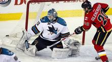 San Jose Sharks goalie Antti Niemi, left, watches Calgary Flames' Curtis Glencross shot go wide. (Jeff McIntosh/The Canadian Press/Jeff McIntosh/The Canadian Press)