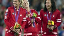 Canadian players Christine Sinclair, Sophie Schmidt and Melissa Tancredi smile on the victory podium after being presented with their Bronze medals at the Olympic Games (Frank Gunn/THE CANADIAN PRESS)