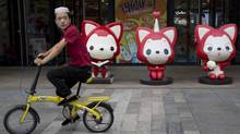 A man rides past cartoon mascots outside a shopping mall in Beijing. (Ng Han Guan/Associated Press)