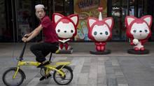 A man rides past cartoon mascots outside a shopping mall in Beijing. (Ng Han Guan/Associated Press)