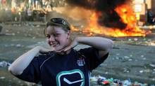 A Canucks fan poses for photos in front of an overturned pickup truck as it burns in downtown Vancouver after Game 7 of Stanley Cup finals on June 15, 2011. (ANTHONY BOLANTE/REUTERS)