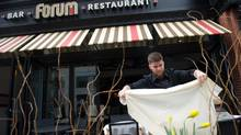 Server Jon Erickson places table cloths on the patio of Boston's Forum restaurant, Friday, April 11, 2014. The second of the Boston Marathon bombs went off outside of the Forum, forcing the restaurant to close for four months. (Gretchen Ertl for the globe and mail)