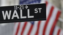 This July 9, 2015 photo shows a Wall Street sign near the New York Stock Exchange in New York. (Seth Wenig/AP)