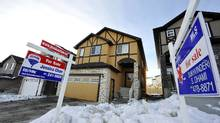 For sale signs in front of homes in Calgary. (Todd Korol for The Globe and Mail/Todd Korol for The Globe and Mail)