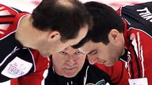 Team Ontario skip Glenn Howard, centre, makes a shot as lead Craig Savill, right, and second Brent Laing sweep during an afternoon draw against New Brunswick at the Tim Hortons Brier in Saskatoon, Sask., Sunday, March, 3, 2012. THE CANADIAN PRESS/Jonathan Hayward (Jonathan Hayward/CP)