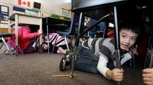 Grade 1 student Joseph Kim takes cover under his desk during an earthquake drill at Hollyburn Elementary School in West Vancouver, B.C., on Jan. 26, 2011. (Darryl Dyck/The Canadian Press)