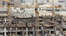 Construction cranes and bulldozers operate at a real estate construction site in Qatar in this photo from September, 2012. (FADI AL-ASSAAD/REUTERS)
