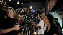 """Director Ruba Nadda (right) gets ready to film a scene for her film """"Inescapable"""" in Johannesburg, South Africa, on March 9, 2012. Filmmakers like Nadda say South African crews are top-notch and the labour, location and equipment costs are low. (Candace Feit)"""