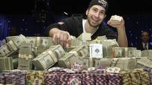 Jonathan Duhamel of Canada poses with prize money and his championship bracelet after beating John Racener of the U.S. in the finals of World Series of Poker Main Event at the Rio hotel-casino in Las Vegas, Nevada November 8, 2010. (STEVE MARCUS/REUTERS)