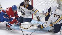 Buffalo Sabres goaltender Ryan Miller makes a save against Montreal Canadiens' Brendan Gallagher, left, as Sabres' Jordan Leopold, right, defends during second period NHL hockey action in Montreal, Saturday, March 23, 2013. (Graham Hughes/THE CANADIAN PRESS)