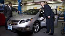 Prime Minister Stephen Harper plugs in a GM Volt electric car for a photo opportunity with President of General Motors Canada Kevin Williams, left and Ontario Premier Dalton McGuinty, right at the General Motors Plant in Oshawa, Ont., on Tuesday July 24, 2012. (Aaron Vincent Elkaim/THE CANADIAN PRESS)