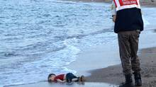 This file photo taken on September 2, 2015, shows a Turkish police officer standing next to a migrant child's dead body, Alan Kurdi, off the shores in Bodrum, southern Turkey after a boat carrying refugees sank while reaching the Greek island of Kos. (NILUFER DEMIR/AFP/Getty Images)