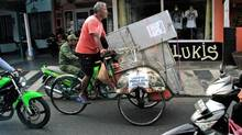 A tricycle driver transports ballot boxes that are being distributed to polling stations in Yogyakarta, Indonesia, Tuesday, July 8, 2014. As the world's third-largest democracy prepares to elect a new president Wednesday, Indonesians are divided between two very different choices: a former furniture maker, Jakarta Governor Joko Widodo and a wealthy ex-army general with close links to former dictator Suharto, Prabowo Subianto. (Slamet Riyadi/AP)