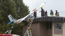 Emergency personal work on a glider plane that crashed onto a mini mart and apartment complex in Langley, British Columbia on September 8, 2013. (BEN NELMS for The Globe and Mail)