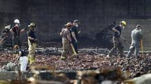 Forensic teams and firefighters continue to work through the rubble in Lac-Mégantic, Que., on July 14, 2013. (PETER POWER/THE GLOBE AND MAIL)