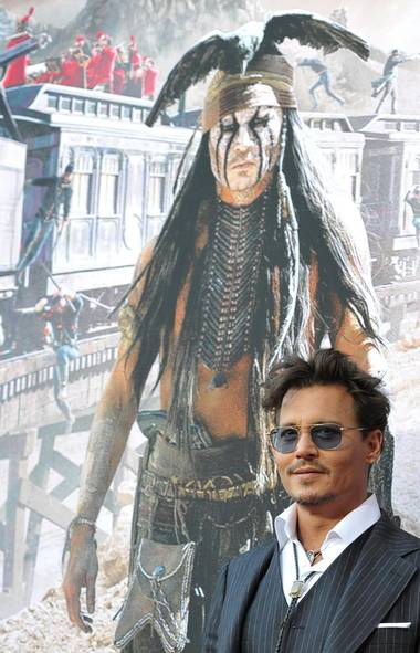 "Johnny Depp stands proudly in front of a picture of his nuanced portrayal in The Lone Ranger of a native American ""spirit warrior"" who speak in wise riddles and poor conjugation, and is the comic sidekick to a white man. (John Shearer/AP)"