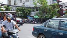 """Our hotel taxi just hit a Phnom Penh police officer. The driver turns back toward us, gulps out a """"Sorrrr-eeeee!,"""" then puts pedal to the metal. We rocket into traffic, but now the officer is on our tail. (Vinh Dao for the globe and mail)"""