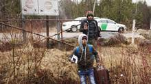 Asylum seekers cross the border from New York into Canada on March 8, 2017 in Hemmingford, Que. (Ryan Remiorz/CP)