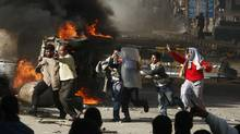 Egyptian demonstrators burn a riot police car during a protest in the northern city of Suez on Jan. 28, 2011 demanding the ouster of President Hosni Mubarak. (-/AFP/Getty Images)