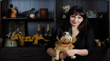 Woofstock president and dog memorabilia collector Marlene Cook holds one of her favourite pieces, an antique French bulldog pulltoy, in front of a case displaying some of the rest of her collection of 8,000 pieces that she estimates is worth $200,000. (Light Monkey Photography/Courtesy of Marlene Cook)