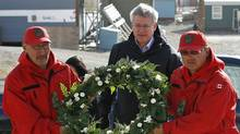 Prime Minister Stephen Harper lays a wreath in Resolute, Nunavut, on Aug. 23, 2011 after a weekend plane crash killed a dozen people. (CHRIS WATTIE/REUTERS)