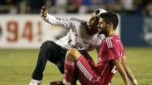 A fan that made it onto the field takes a selfie with Real Madrid's Isco (Tony Gutierrez/AP)