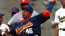 In this Feb. 25, 1999 file photo, Venezuela's President Hugo Chavez, wearing the national baseball team uniform, pitches to Chicago Cubs out fielder Sammy Sosa during a batting exhibition at Universtity Stadium in Caracas, Venezuela. (AP)