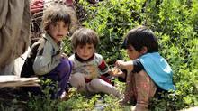 Syrian children play outside their tent at a refugee camp (CAREN FIROUZ/Reuters)