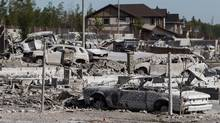Burned-out homes and vehicles are seen in the Timberlea neighbourhood as residents re-enter fire-ravaged Fort McMurray, Alta., on June 2, 2016. (CODIE MCLACHLAN/THE CANADIAN PRESS)
