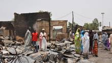 People stand outside burnt houses following an attack by Islamist militants in Gambaru, Nigeria. Many brutalized residents of the once bustling town of Gamboru said Monday May 12, 2014, they are moving across the border to Cameroon because they cannot trust the Nigerian government to protect them, after repeated attacks by Islamist militants, including an attack a few days ago that killed some hundreds of people with more than 1,000 shops, dozens of homes and 314 trucks and cars bombed and burned out. (Jossy Ola/AP)