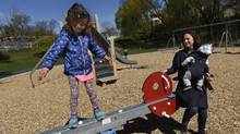 Five-year-old Isabella balances atop a new teeter-totter at the new playground at Ravina Gardens Park, while her mother, Elena Yunusov, minds her baby brother on May 3. (Fred Lum/The Globe and Mail)