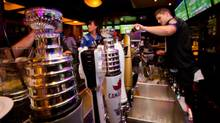 Stanley Cup are used as handles on a beer taps as bartender James Vine pours a drink at the Shark Club sports bar in downtown Vancouver, B.C., on Thursday September 13, 2012. (DARRYL DYCK)