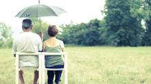 couple sit on the meadow under umbrella (bajker/Getty Images/iStockphoto)