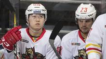 Kunlun Red Star's Rudi Ying, left, and Alexei Ponikarovsky sit on the bench during the Kontinental Hockey League match between Spartak and Kunlun Red Star, in Moscow, Russia, Saturday, Oct. 1, 2016. (Pavel Golovkin/The Associated Press)