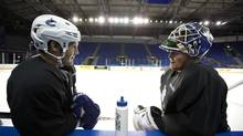 Vancouver Canucks defencemen Andrew Alberts and goaltender Cory Schneider chat during a break from practice in Vancouver on Tuesday. (Deborah Baic/The Globe and Mail)