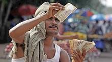 With its growing dependence on imports, and populist programs that fuel inflation, India faces a slew of problems that can only put downward pressure on the rupee. (Biswaranjan Rout/Associated Press)