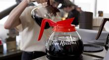 A server pours a cup of coffee at the Tim Hortons' AGM in Toronto on Thursday, May 10, 2012. (Chris Young/CP)