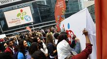 A crowd of people sign a mural with the new logo on it during the official launch of the 2015 Pan/Parapan American Games where a street party which was held at Maple Leaf Square in Toronto, Ontario, Canada. (Deborah Baic/The Globe and Mail/Deborah Baic/The Globe and Mail)