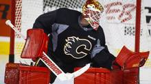 Calgary Flames goalie Brian Elliott makes a save during an on-ice session on the second day of training camp in Calgary, Friday, Sept. 23, 2016. Acquired in a draft-day deal for a second-round and a conditional pick, the 31-year-old from Newmarket, Ont., and free-agent signing Chad Johnson were the off-season solutions to Calgary's goaltending woes. (Jeff McIntosh/THE CANADIAN PRESS)