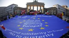 "Demonstrators stretch a banner reading ""For jobs and solidarity in Europe. No to austerity"" during an anti-austerity protest in front of the Brandenburg Gate in Berlin in this Nov. 14, 2012, file photo. (PAWEL KOPCZYNSKI/REUTERS)"