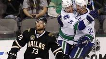Vancouver Canucks Alexandre Burrows (14) and Henrik Sedin (33) celebrate Henrik's goal as Dallas Stars Alex Goligoski skates past during the third period of their NHL game in Dallas, Texas February 21, 2013. (MIKE STONE/REUTERS)