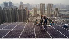 Employees from Wuhan Guangsheng Photovoltaic Company work on a solar panel project on the roof of a a new development on May 15 in Wuhan, China. China's coal consumption has fallen for three consecutive years and it appears on course to far exceed its 2030 carbon-emissions-reduction pledge. (Kevin Frayer/Getty Images)