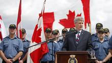 Prime Minister Stephen Harper talks to crew members during a visit to HMCS Ville de Quebec, anchored off Port of Spain, on November 29, 2009. (CHRIS WATTIE)